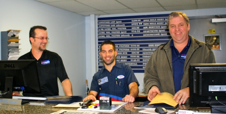 Richard, Iman and Paul smiling from behind the Butler Ford service desk.